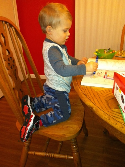 Sporting his new kicks while coloring - a Cars coloring book, of course.